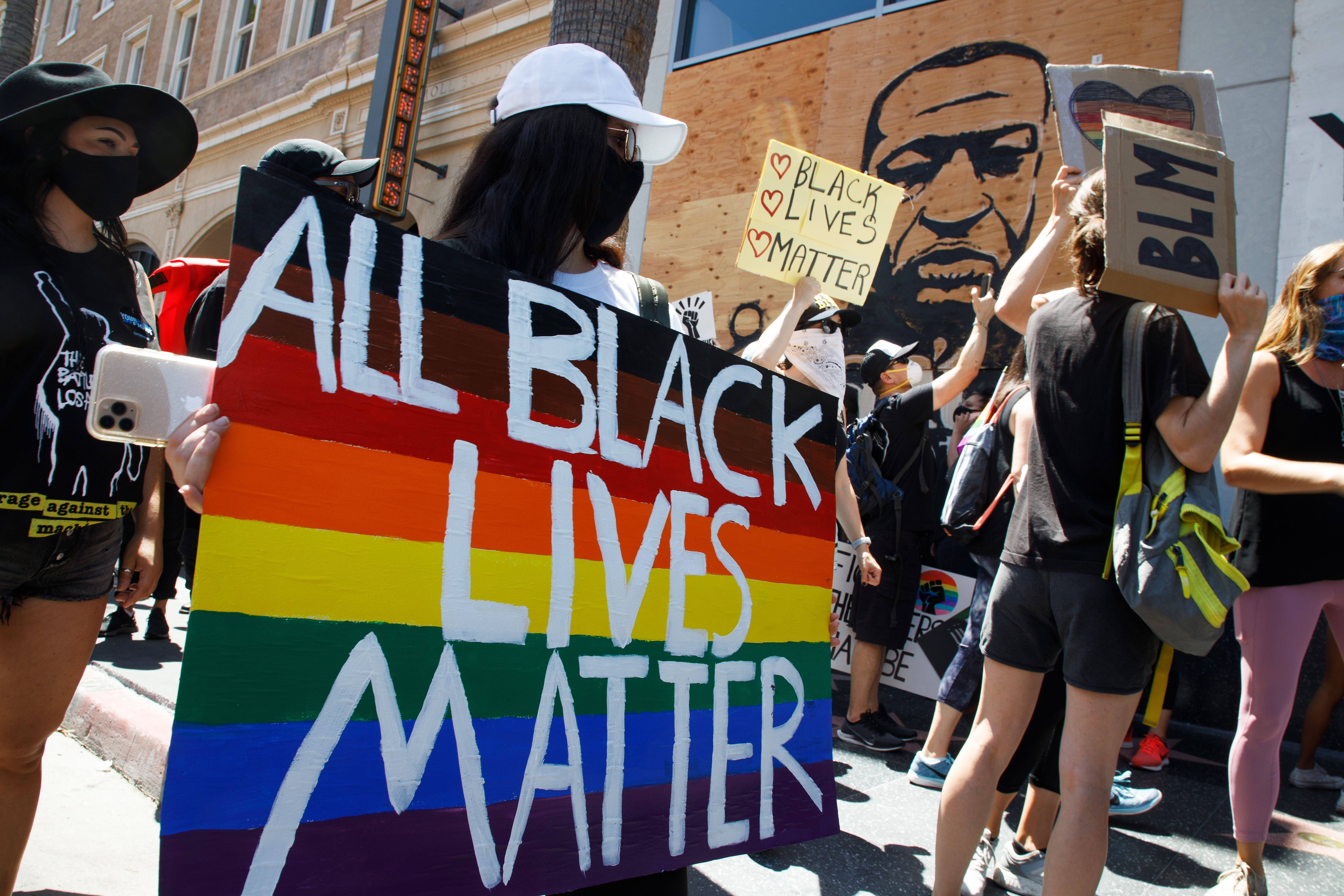 Black Lives Matter protest woman holding rainbow pride side