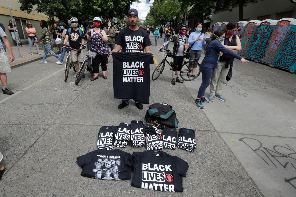 Man sells Black Lives Matter T-shirts, inside what has been named the Capitol Hill Occupied Protest (CHOP) zone in Seattle. Protesters calling for police reform and other demands have taken over several blocks near downtown Seattle after officers withdrew from a police station in the area following violent confrontations. The CHOP name is a change from CHAZ (Capitol Hill Autonomous Zone) that was used earlier in the weekAmerica Protests Demonstrations, Seattle, United States - 14 Jun 2020