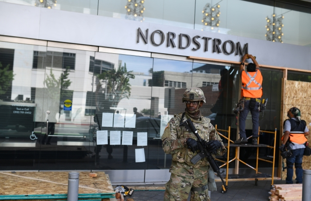 Nordstrom in Santa Monica under the watch of National Guard as its boarded up Monday.