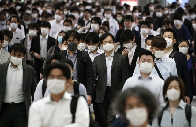 A Tokyo station is crowded with commuters wearing face mask during rush hour, May 2020.