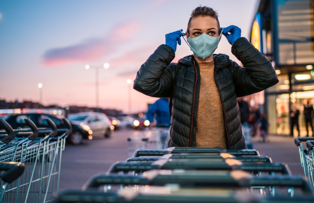 Woman with protective gloves puts a medical mask on her face as a virus protection in a supermarket parking lot.