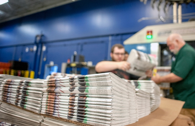 FILE - In this April 11, 2018, file photo, production workers stack newspapers onto a cart at the Janesville Gazette Printing & Distribution plant in Janesville, Wis. The U.S. Commerce Department is going ahead with a tax on Canadian newsprint, a threat to the already-struggling American newspaper industry. The tariffs unveiled Thursday, Aug. 2, are mostly lower than those originally announced earlier this year but would still impose an anti-dumping border tax as high as 16.88 percent. (Angela Major/The Janesville Gazette via AP, File)