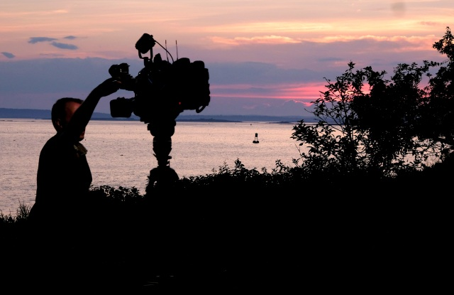 A member of a TV crew adjusts their camera while filming near the shore of Bailey Island, Maine, where a woman swimming off the coast was killed in an apparent shark attack Monday, July 27, 2020. Two kayakers helped the person get to shore, and an ambulance provided further assistance, but she was pronounced dead at the scene, Marine Patrol said. (AP Photo/Jim Gerberich)