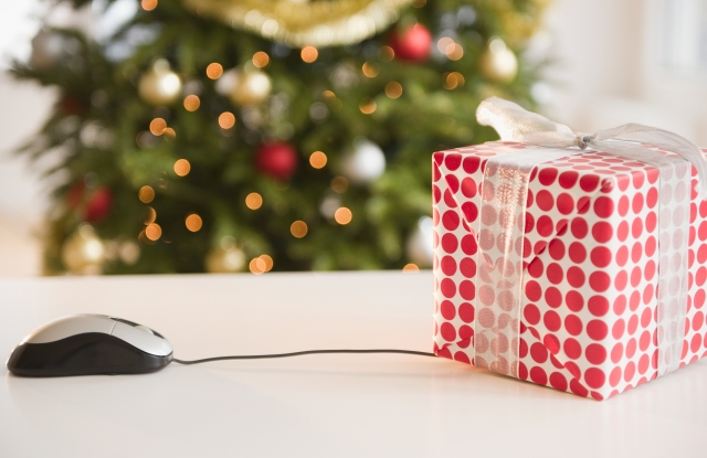 Computer mouse connected to Christmas gift (Photo by: Tetra Images/AP Images)