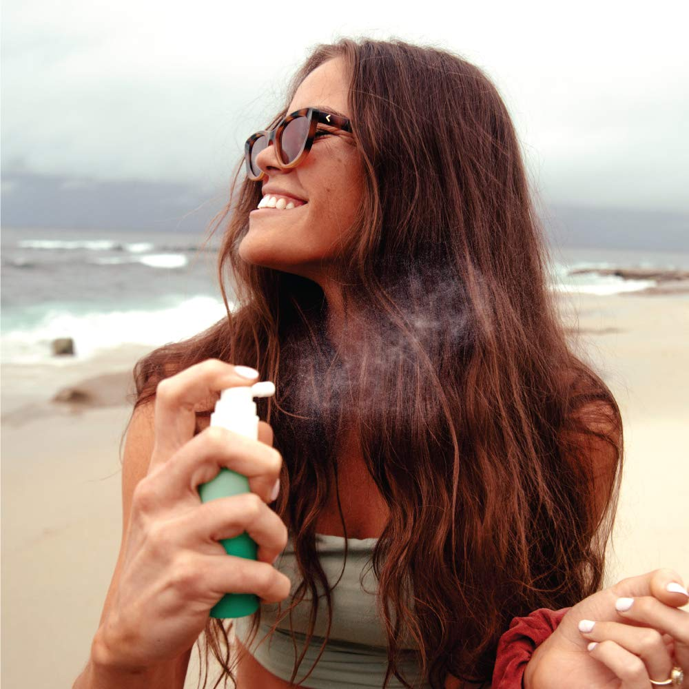 A woman applying the COOLA Organic Scalp & Hair Sunscreen Mist at the beach