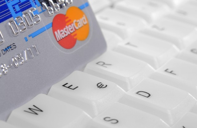 Credit card standing on a computer keyboard, symbolic image for internet shoppingVARIOUS