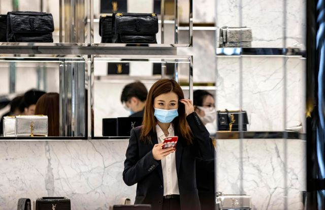 A woman wearing a protective face mask stands at Yves Saint Laurent shop in Guangzhou.