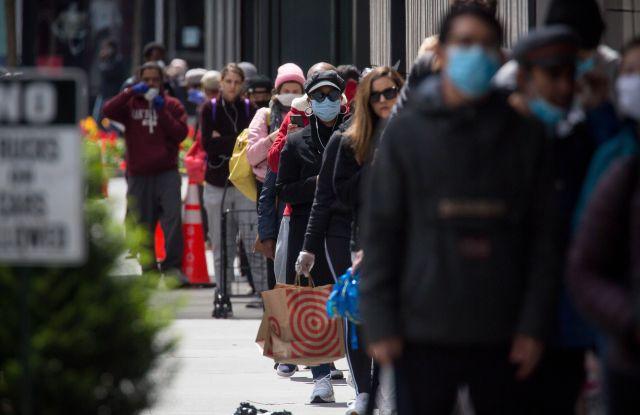 People wearing face masks wait in line shop.