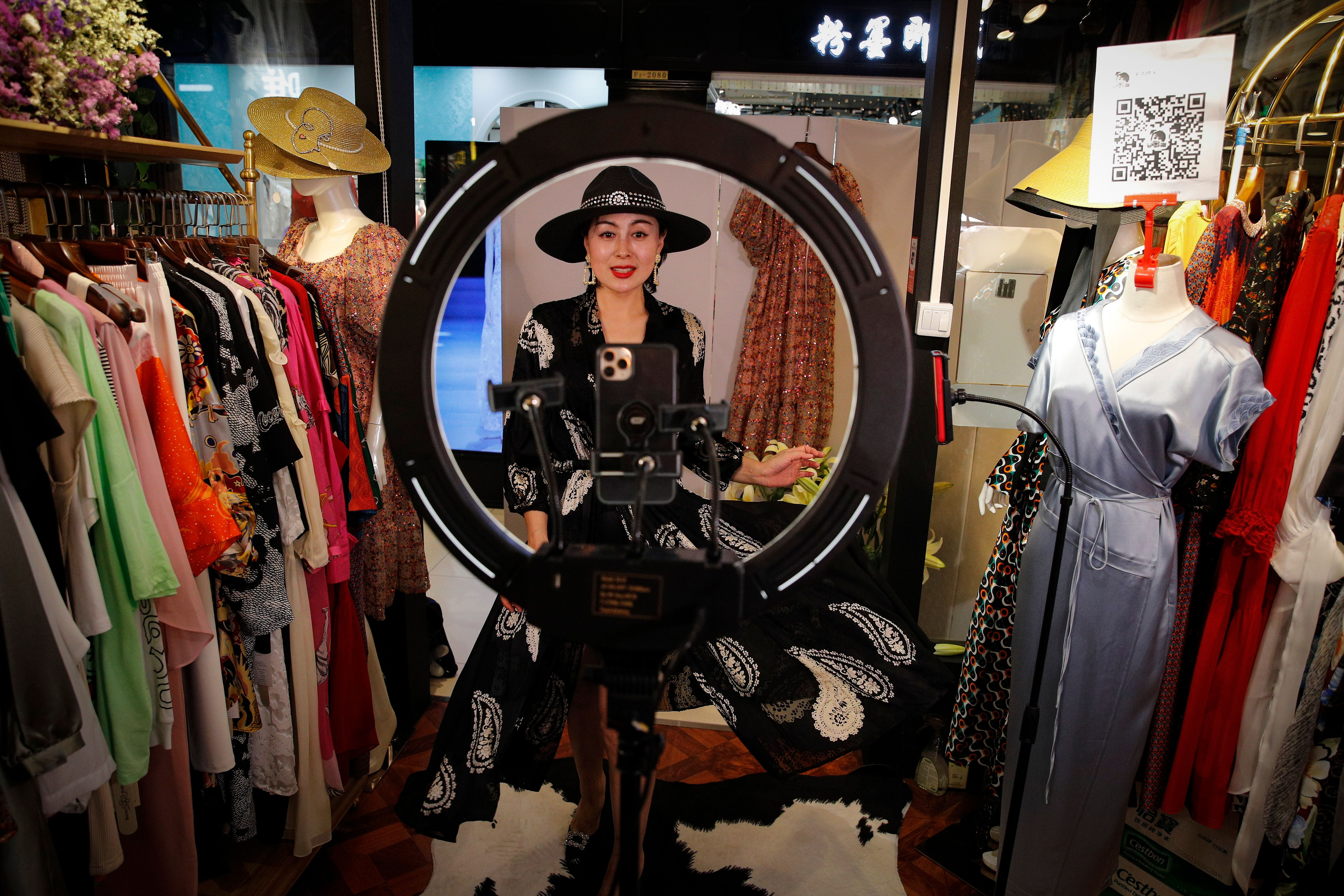 A shop owner showed her fashion dresses for her online clients during the live-streaming.