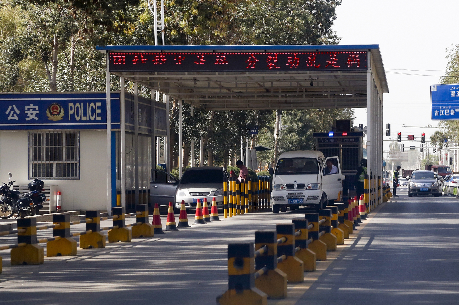 In this Sept. 21, 2018, photo, Uighur drivers have their vehicles checked at a police check point in Hotan, in western China's Xinjiang region.