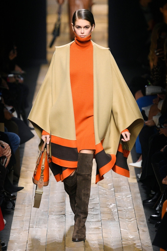 """Kors' fall collection was all about cozy luxury, including several looks that should feel as if """"you're wrapped up in the chicest security blanket in the world."""" On the runway, Kaia Gerber wore a variation of a poncho designed 24 years ago. Though Kaia's mother, Cindy Crawford, walked that show, Naomi Campbell wore the original wrap."""