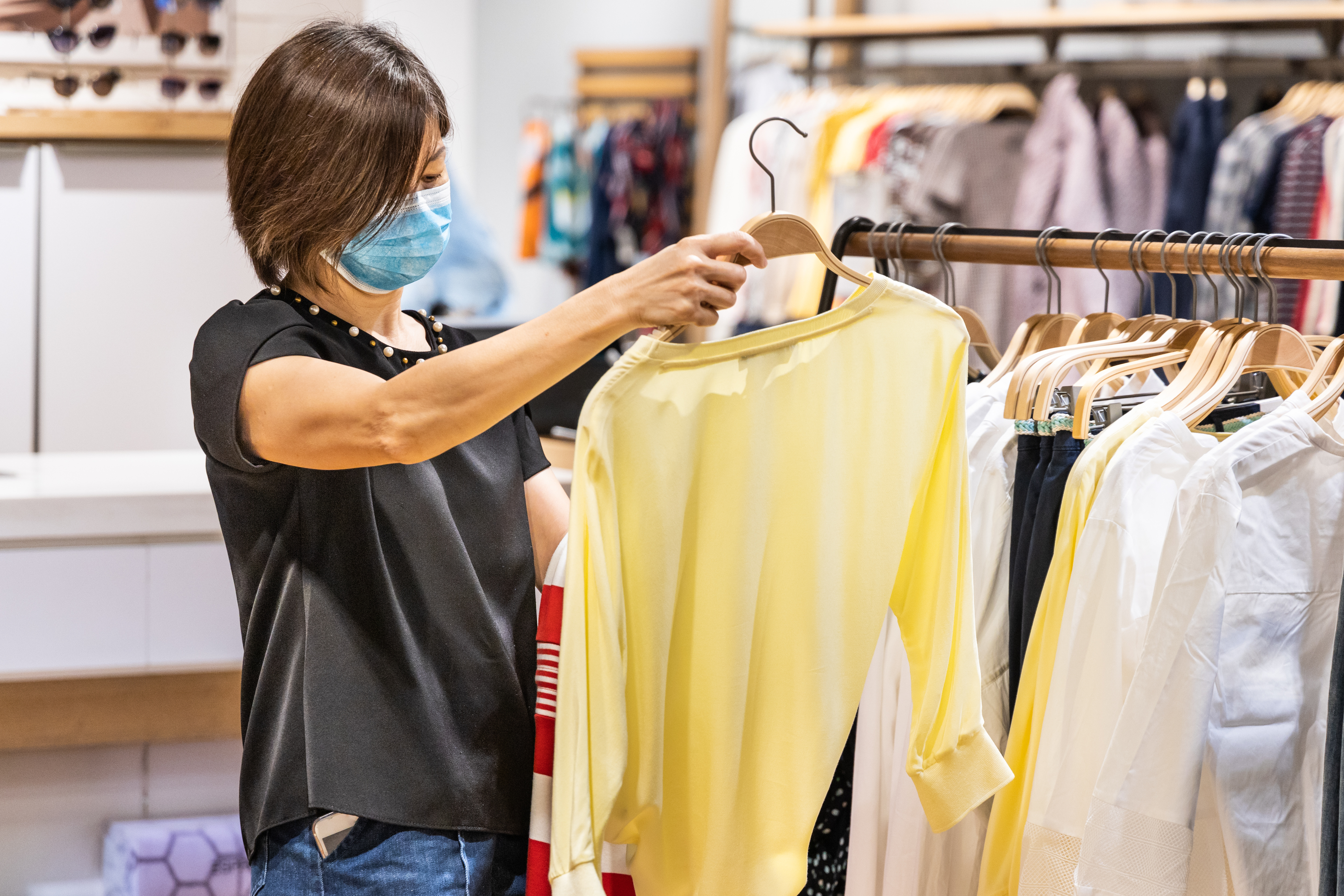 woman shopping apparels in clothing boutique with protective face mask as new normal requirement in Malaysia