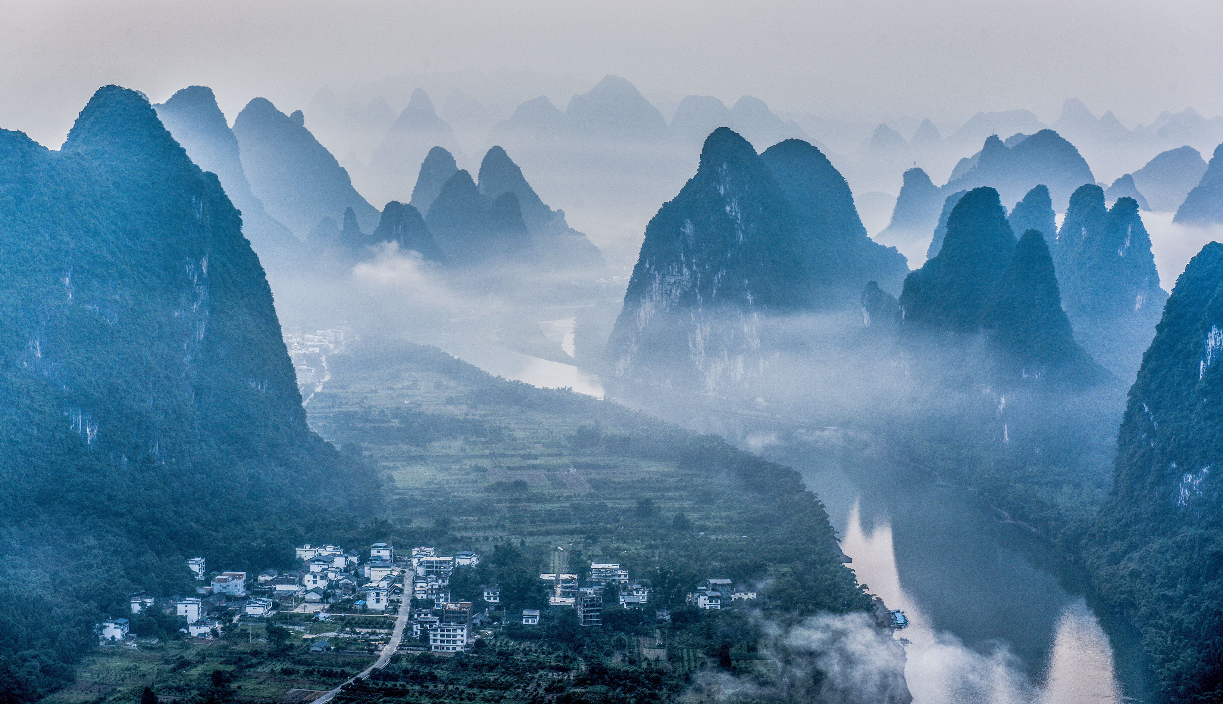 The mountains and hills are surrounded by mist and cloud along the Li River at sunrise in Yangshuo county.