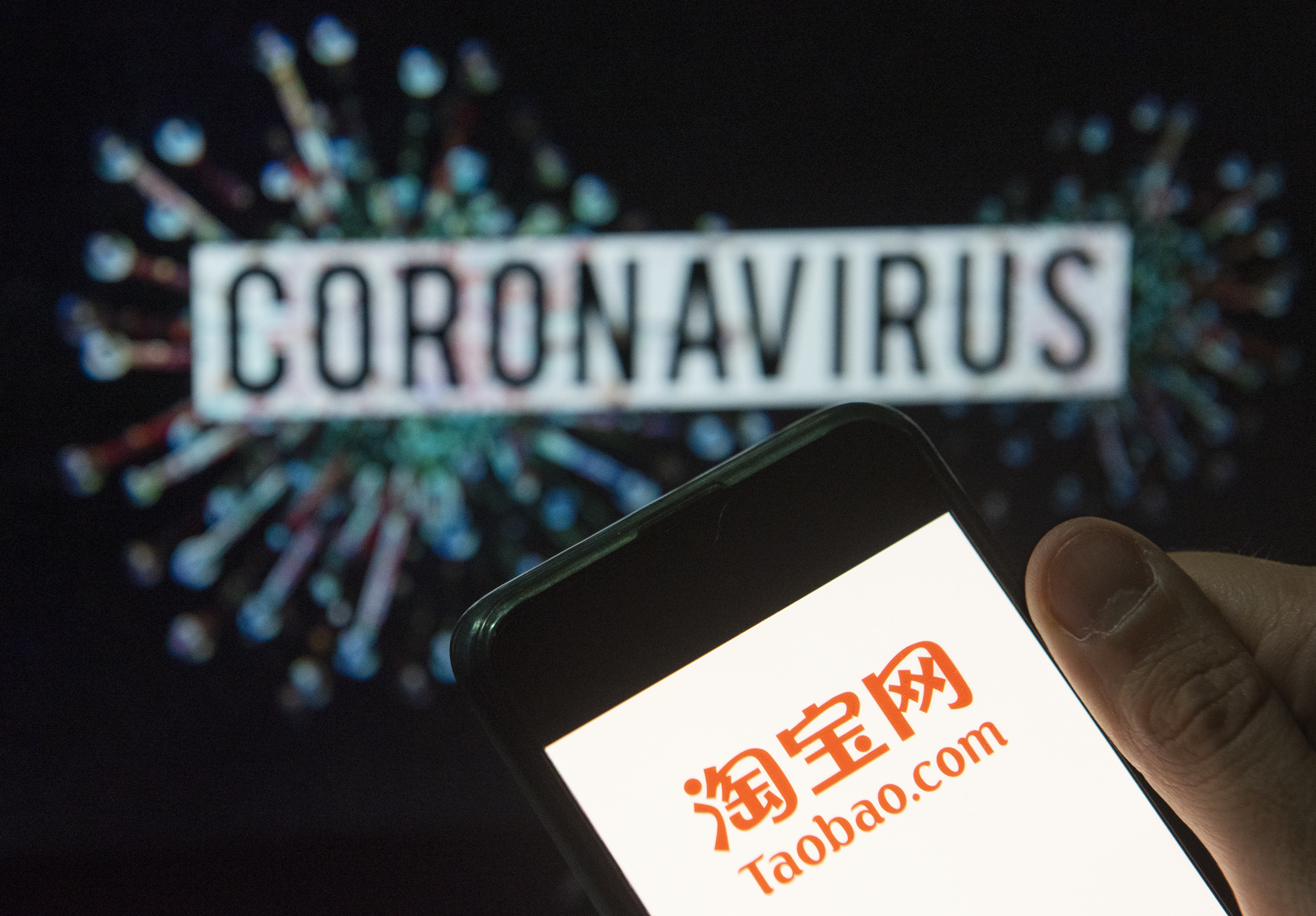 ATaobao logo displayed on a smartphone with a computer model of the COVID-19 coronavirus on the background.