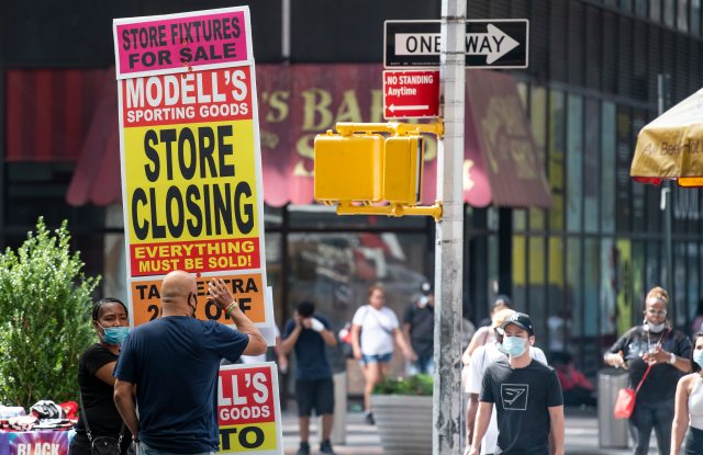August 08, 2020: An overall view of a Mid-Town street corner with a person holding a store closing sign as business struggle to stay in business in Manhattan, New York. Mandatory credit: Kostas Lymperopoulos/CSM (Credit Image: © Kostas Lymperopoulos/CSM via ZUMA Wire) (Cal Sport Media via AP Images)