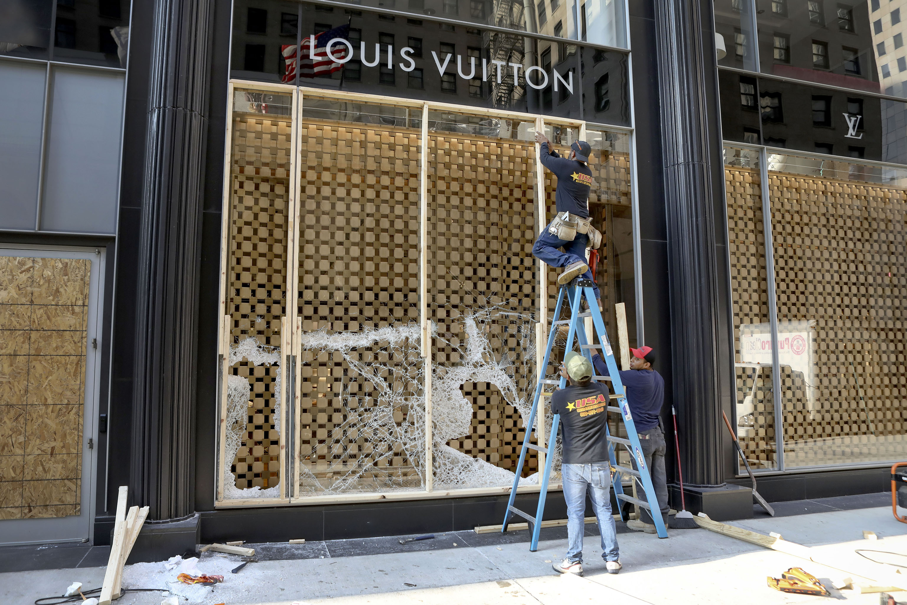 Workers begin to board up a display window at the Louis Vuitton store Monday, Aug. 10, 2020, after overnight vandals hit many high-end stores in Chicago. Chicago's police commissioner says more than 100 people were arrested following a night of looting and unrest that left several officers injured and caused damage in the city's upscale Magnificent Mile shopping district and other parts of the city. (AP Photo/Teresa Crawford)