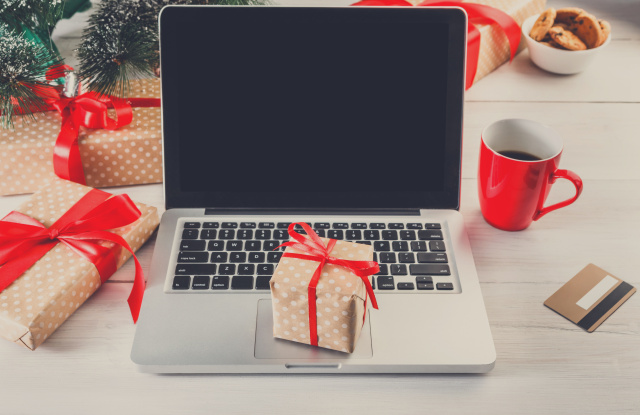 Christmas online shopping. Laptop with copy space on screen lay on white wood, present boxes and christmas tree on background. Internet commerce on winter holidays concept