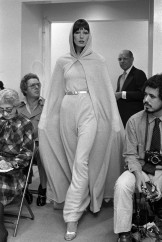 Anjelica Huston models a belted knit gown and matching hooded cape on the runway of the Halston resort 1972 RTW collection.