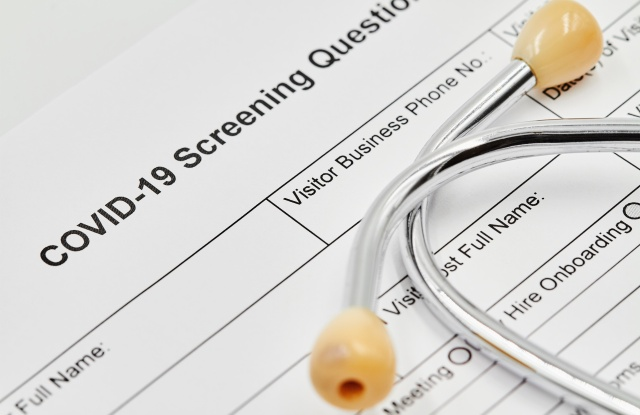 COVID-19 Screening questionnaire form with stethoscope on it. Closeup.