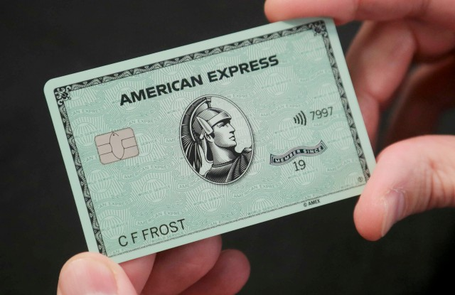 """In this Wednesday, Oct. 23, 2019, photo Ira Galtman, American Express director of corporate archives, shows the new American Express """"Green Card,"""" in New York. For 50 years, """"Green Card"""" was everywhere and now it's getting a much-needed revamp, with a new look and more travel benefits. (AP Photo/Bebeto Matthews)"""