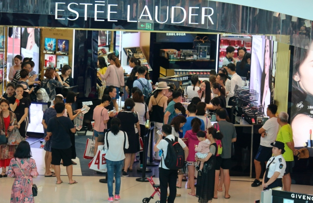 Customers shop at a cosmetics store of Estee Lauder in a duty-free shop at Haitang Bay, in Sanya city, south China's Hainan province.