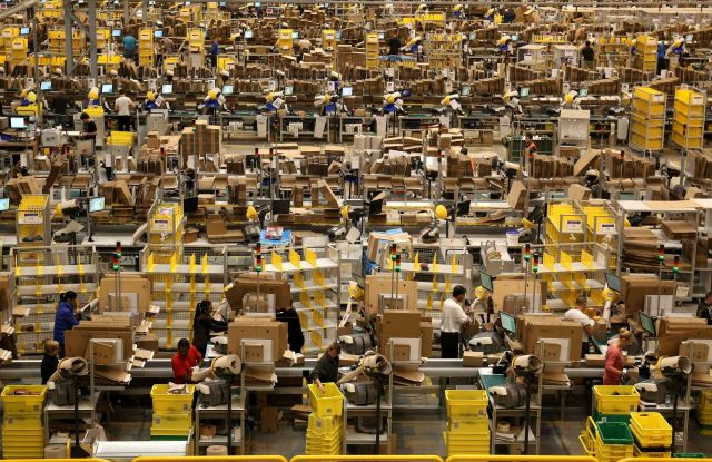 Amazon workers packing orders on the warehouse floor at the Amazon UK Fulfilment Centre in Peterborough, Cambridgeshire.
