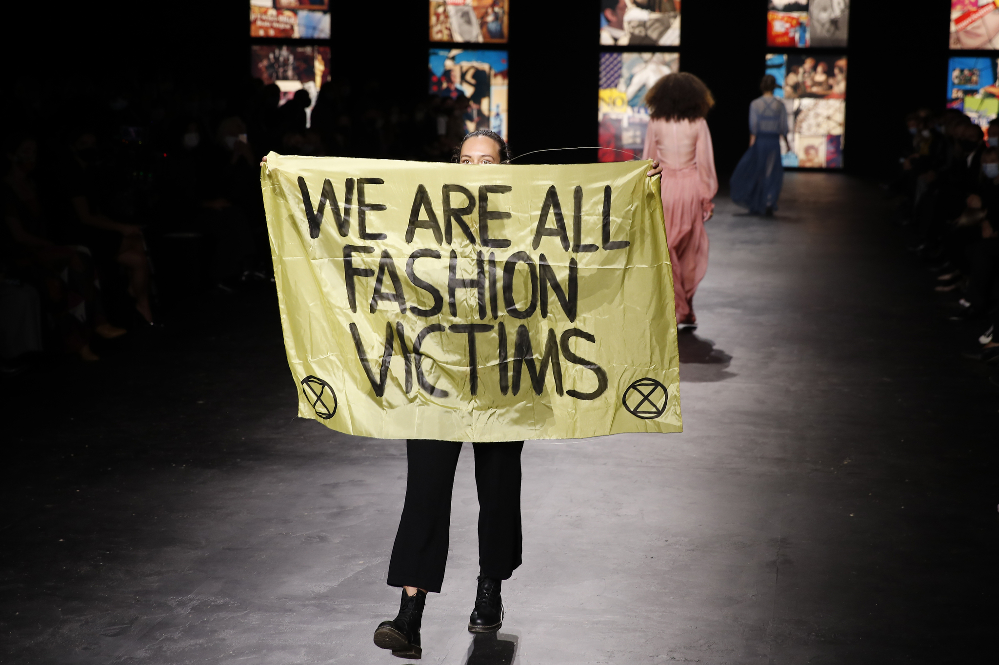 An activist displays a banner during Dior's Spring 2021 show.