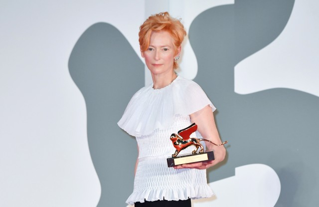 Tilda Swinton poses on the red carpet with the Golden Lion Lifetime achievement award after the Opening Ceremony during the 77th Venice Film Festival.