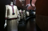 "Caption: Chanel tweed suits are displayed in the new ""Gabrielle Chanel Galleries"" at Palais Galliera."