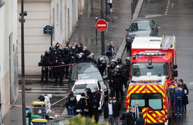 Police officers gather in the area of a knife attack near the former offices of satirical newspaper Charlie Hebdo, Friday Sept. 25, 2020 in Paris. Paris police say they have arrested a man suspected of a knife attack that wounded at least two people near the former offices of satirical newspaper Charlie Hebdo. Police initially thought there were two attackers but now say there was only one.  (AP Photo/Thibault Camus)