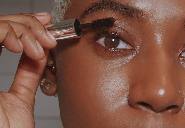 A woman applying the Peter Thomas Roth Lashes To Die For Turbo Nighttime Eyelash Treatment