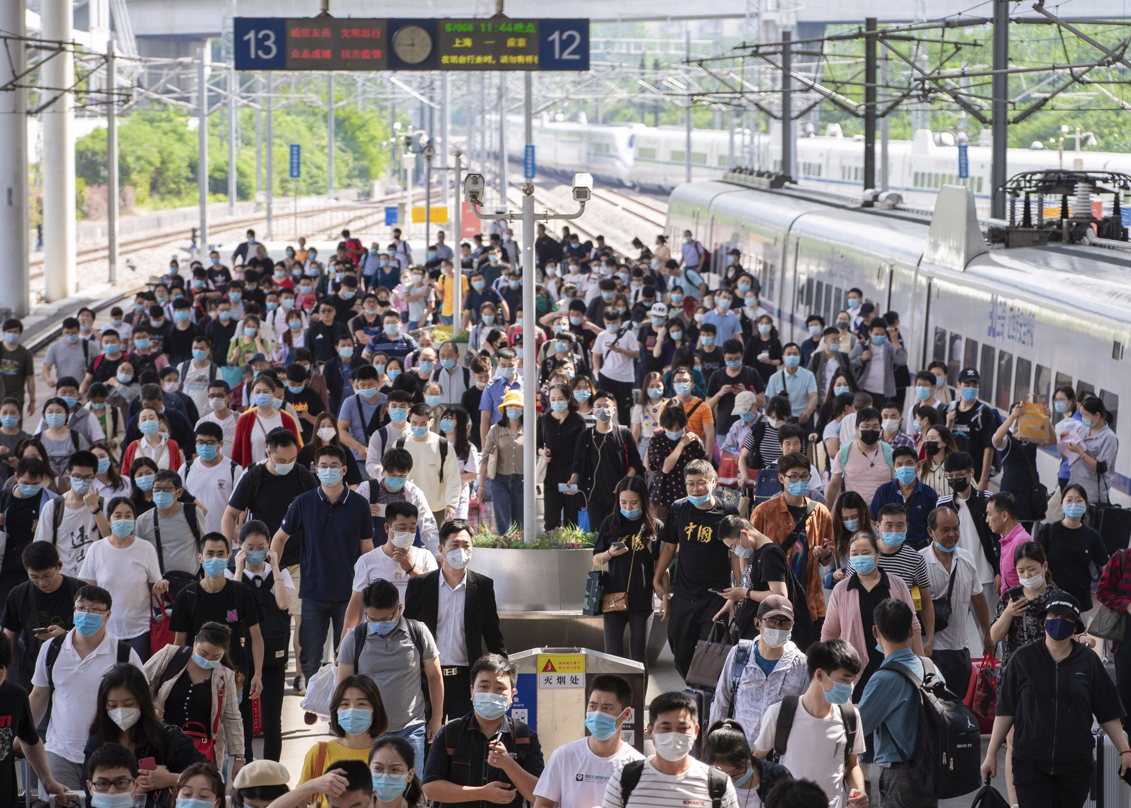 """Passengers get off a train at a railway station in Nanjing in east China's Jiangsu province ahead of the """"Golden Week"""" national holiday."""