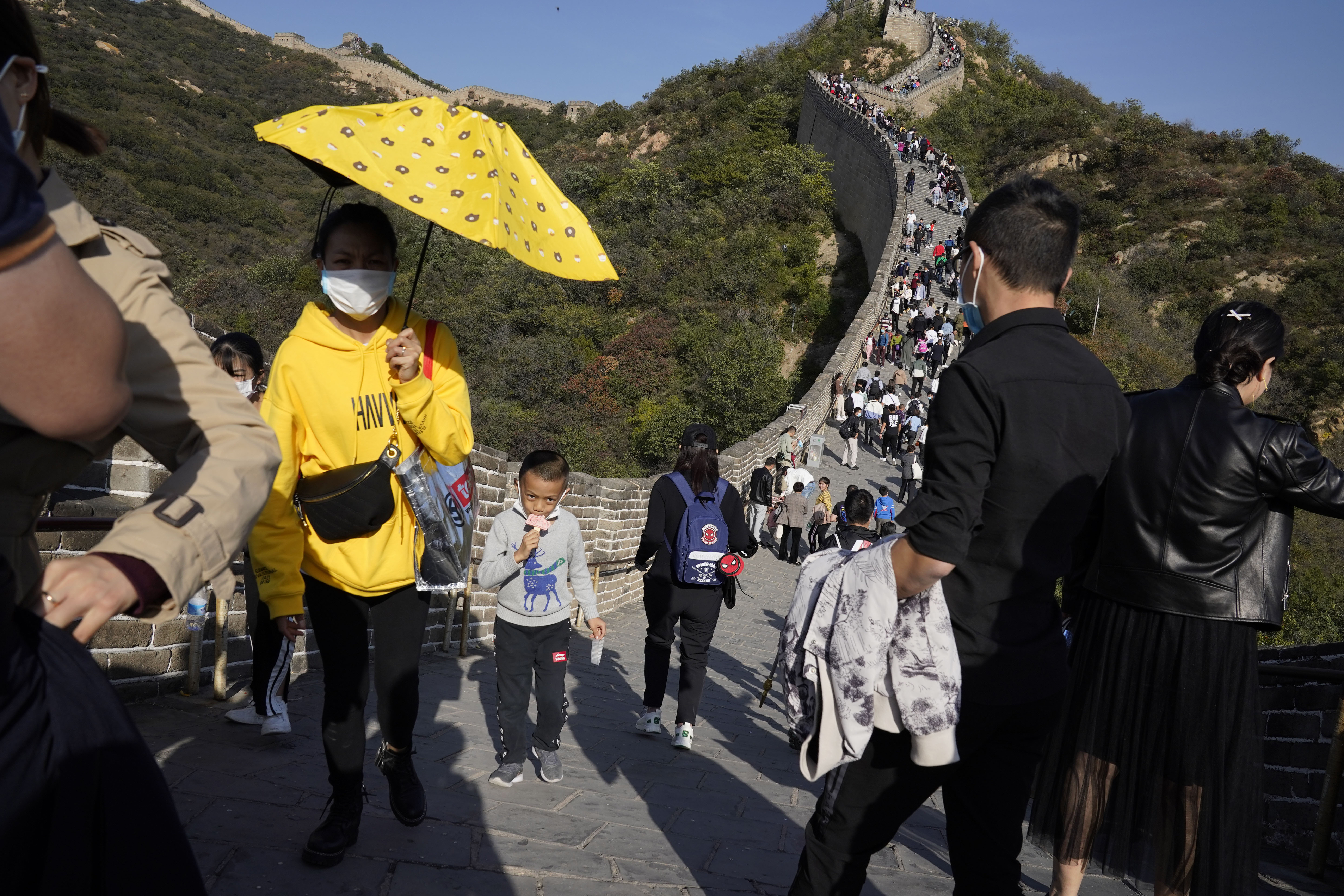 """A child lowers his mask to enjoy an ice cream as he climbs up a stretch of the Badaling Great Wall of China on the outskirts of Beijing during the """"Golden Week"""" national holiday."""
