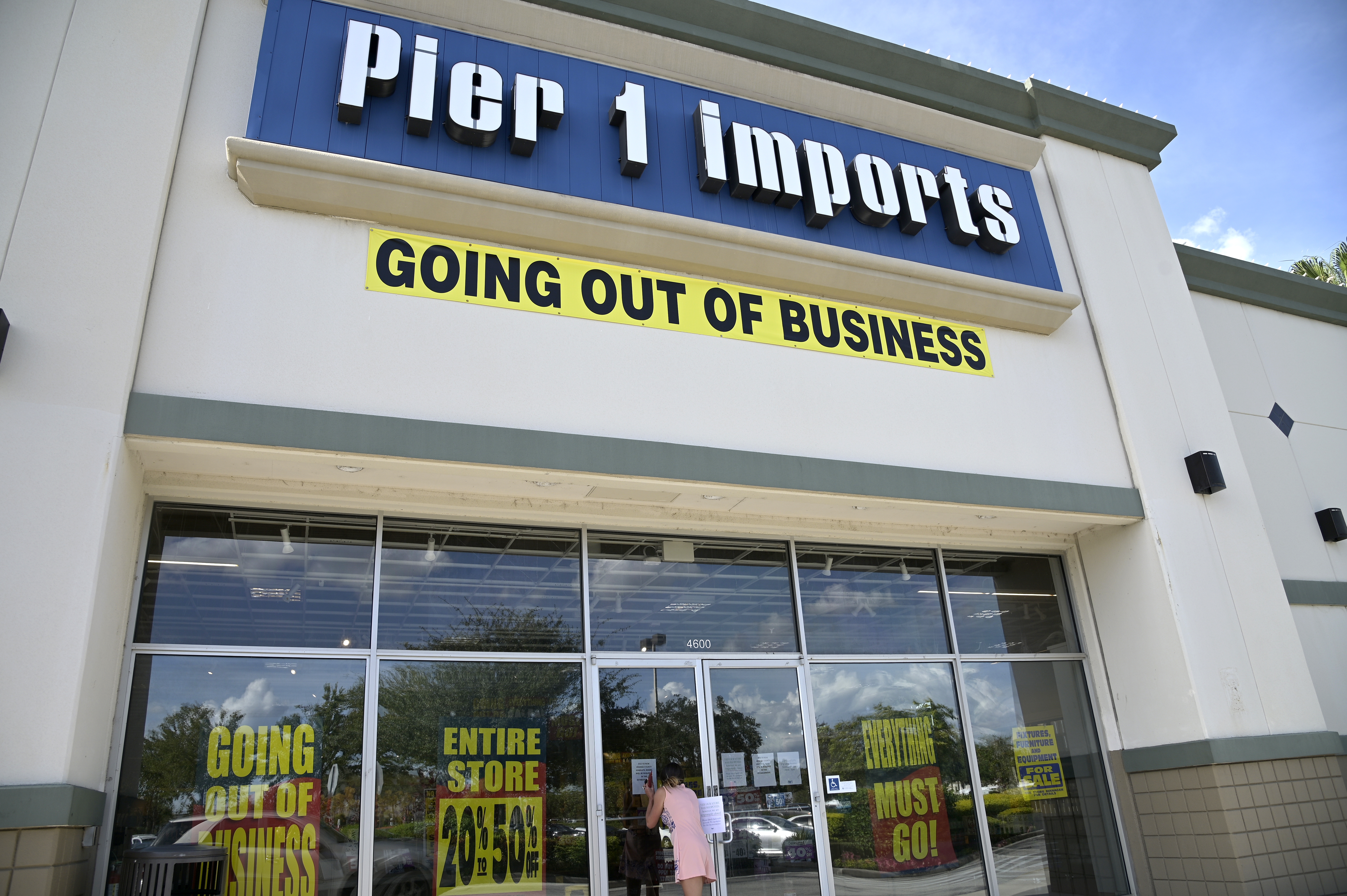 A shopper peers into a closed Pier 1 Imports store, Monday, Aug. 3, 2020, in Orlando, Fla. The chain plans to shutter all stores and liquidate due to COVID-19. Many beaches and businesses have reopened during the new coronavirus pandemic. (Phelan M. Ebenhack via AP)