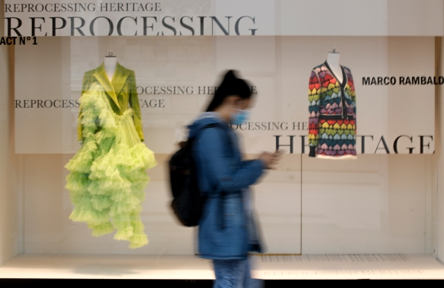 A woman wearing a mask walks past Milan's landmark department store, Rinascente, as young stylists present their collections, in Milan, Italy, Wednesday, Sept. 23, 2020. The Italian fashion industry is trying to inject optimism into the most dismal year on record for the luxury sector, staging 23 live runway shows and 37 presentations during a hybrid live-digital Milan Fashion Week that aims to excite consumers and connect with buyers. (AP Photo/Luca Bruno)