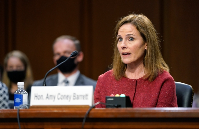 Supreme Court nominee Amy Coney Barrett speaks during a confirmation hearing before the Senate Judiciary Committee, Tuesday, Oct. 13, 2020, on Capitol Hill in Washington. Her family looks on at left. (AP Photo/Patrick Semansky, Pool)