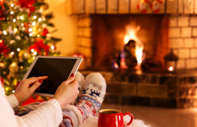 Woman sitting by fireplace and christmas tree holding tablet cozy concept