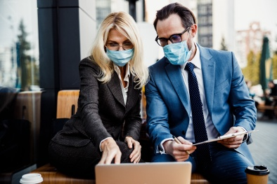 Front view of two people in eyeglasses and protective masks sitting in a street cafe