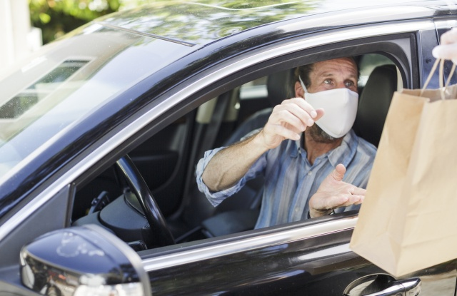 Bags passed through car window to driver wearing mask