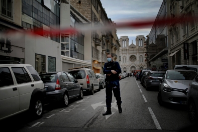 A French policeman stands guard near the scene of the knife attack at the Notre Dame church in Nice, France.