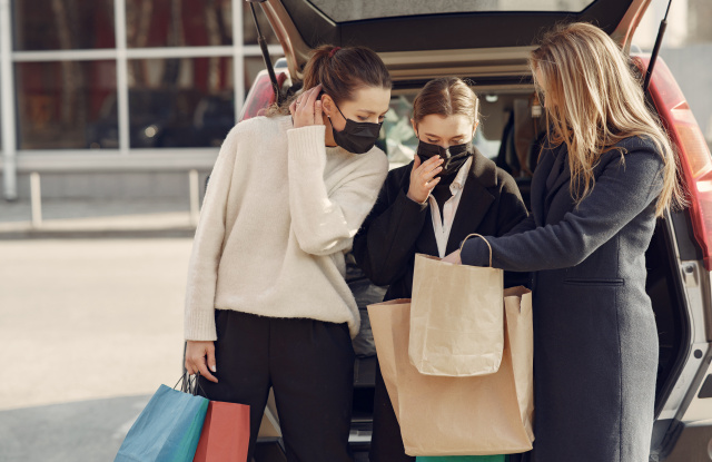 Girls on a shopping. People in a masks. Women with a shopping bags. Lady near trunk of the car. Coronavirus theme.