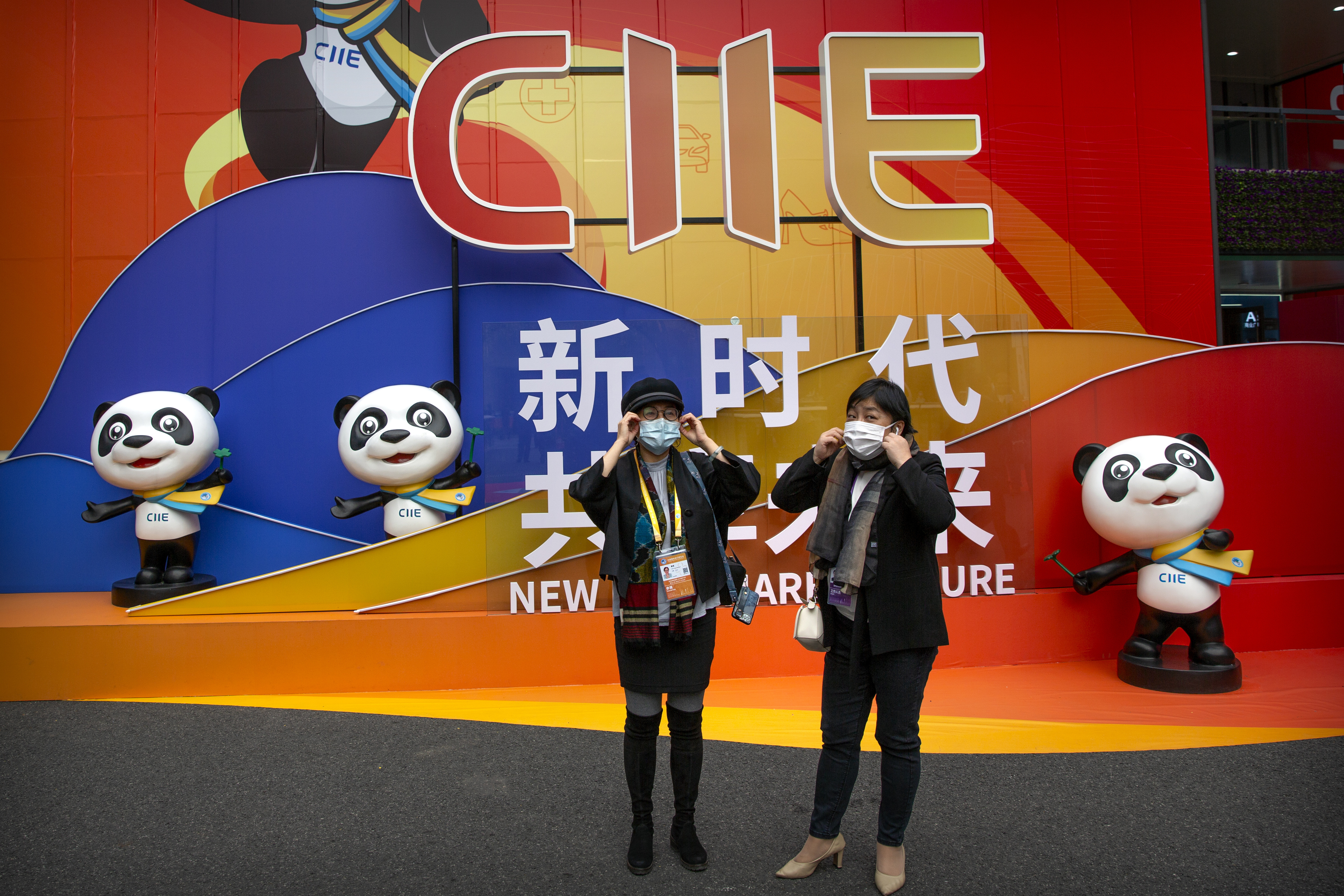 Women adjust their face masks as they stand in front of a display at the China International Import Expo in Shanghai, Thursday, Nov. 5, 2020. The expo, one of China's largest annual trade fairs, kicked off on Thursday as the ongoing COVID-19 pandemic has largely been controlled within China. (AP Photo/Mark Schiefelbein)