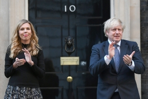 Coronavirus - Thu May 14, 2020. Prime Minister Boris Johnson and his partner Carrie Symonds, stand in Downing Street, London, to join in the applause to salute local heroes during Thursday's nationwide Clap for Carers to recognise and support NHS workers and carers fighting the coronavirus pandemic. Picture date: Thursday May 14, 2020. See PA story HEALTH Coronavirus. Photo credit should read: Victoria Jones/PA Wire URN:53750973 (Press Association via AP Images)