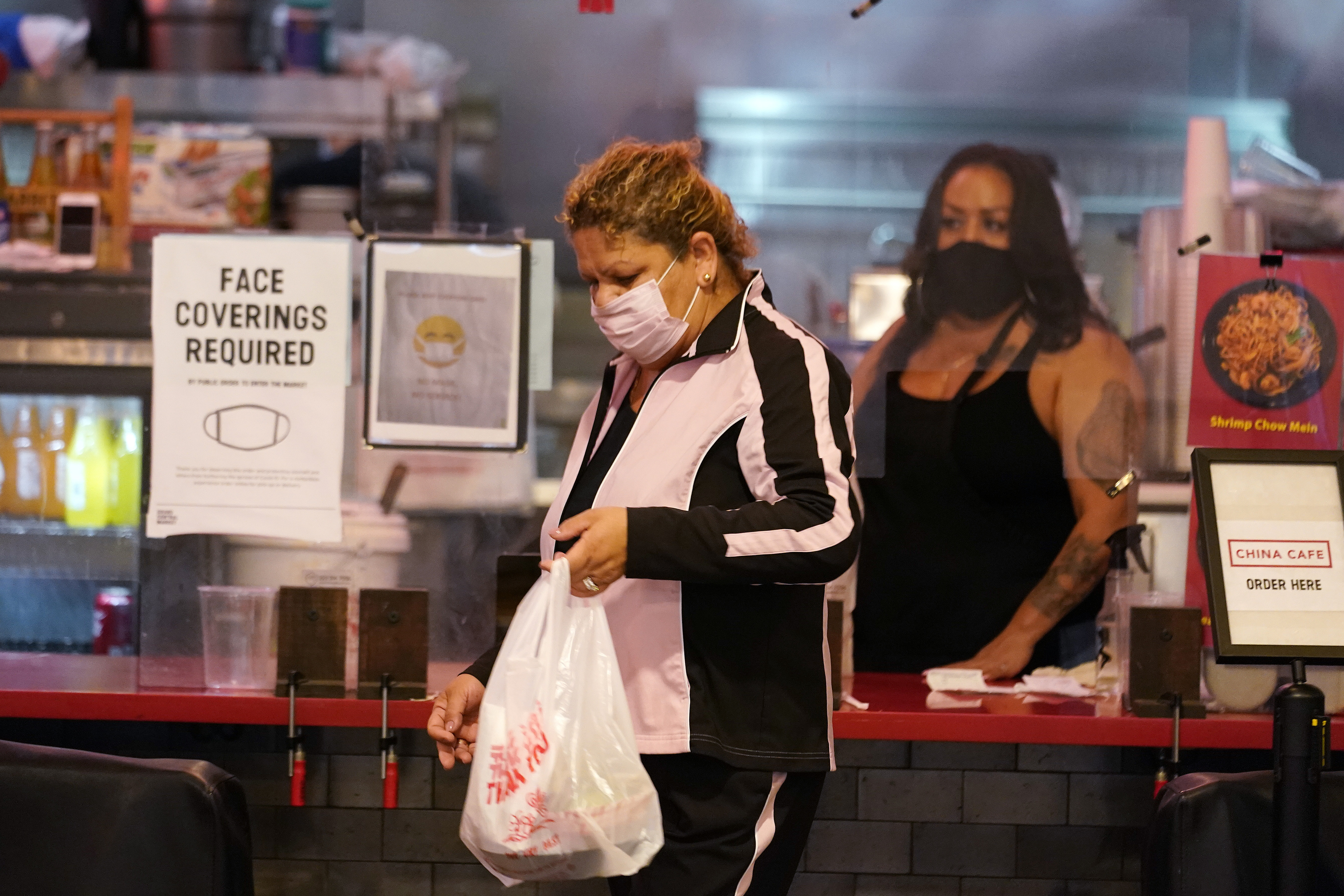 A customer picks up food at the Grand Central Market Monday, Nov. 16, 2020, in Los Angeles. California Gov. Gavin Newsom announced Monday, Nov. 16, 2020, that due to the rise of COVID-19 cases, Some counties have been moved to the state's most restrictive set of rules, which prohibit indoor dining. The new rules begin, Tuesday, Nov. 17. (AP Photo/Marcio Jose Sanchez)