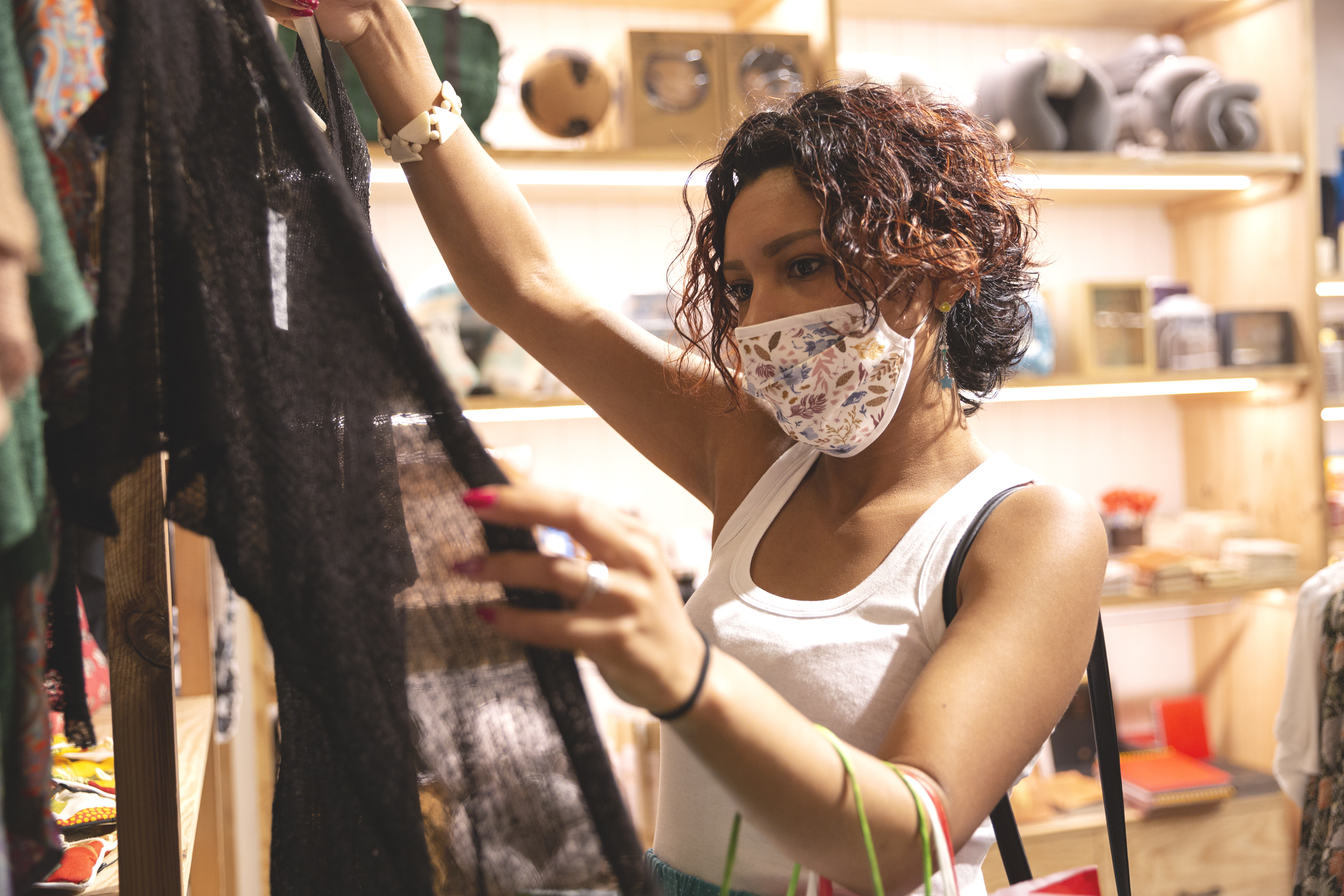 Woman with a face mask looking at clothes inside a store. Selective focus. Concept of new normality.