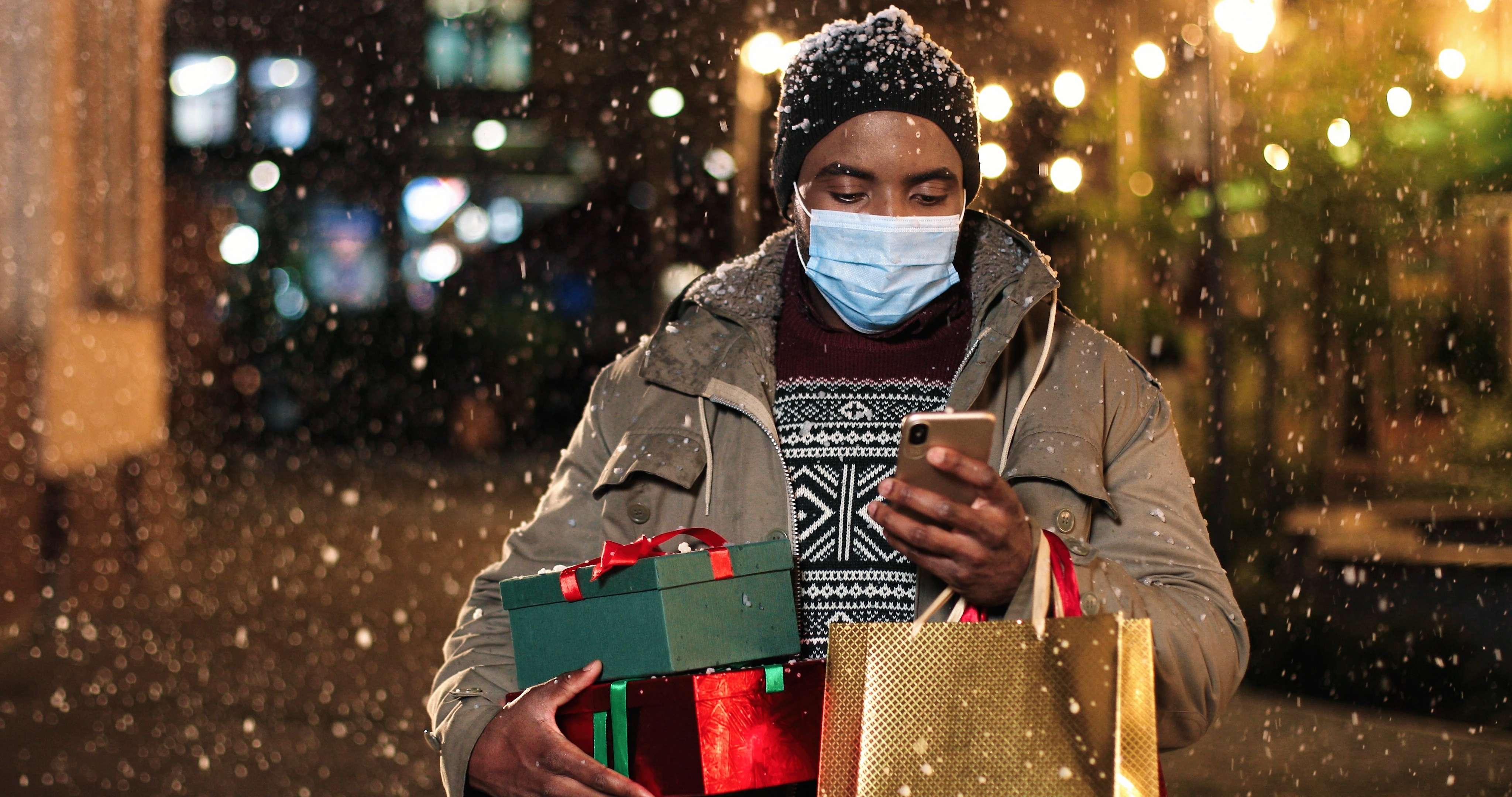 Portrait of man standing and texting on mobile phone. Young African American happy male with little Christmas tree and shopping bags typing on smartphone while snowing. Winter holidays concept