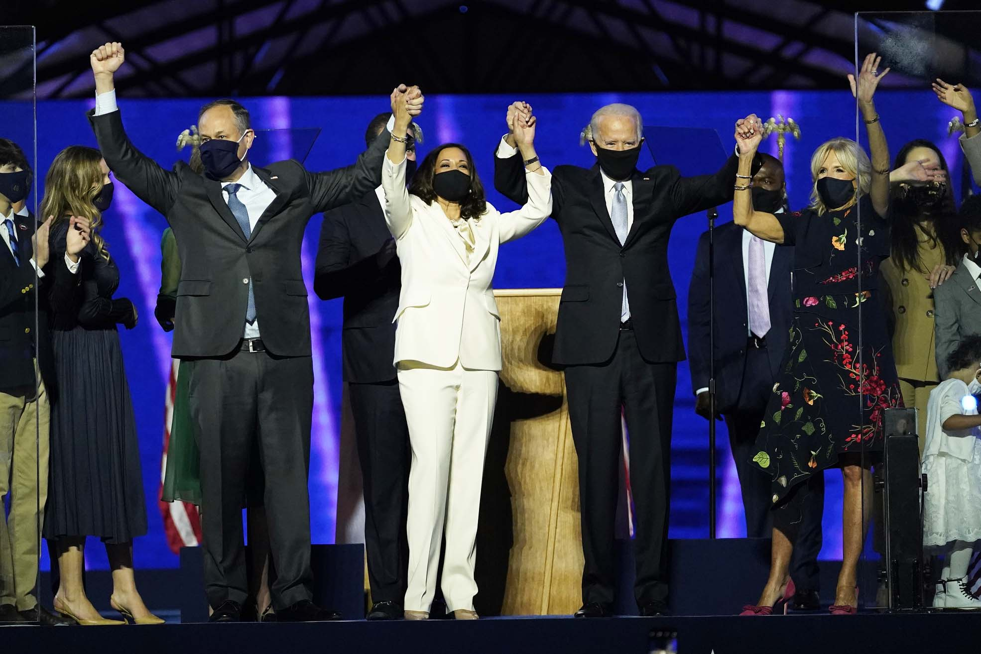 From left, Doug Emhoff, husband of Vice President-elect Kamala Harris, Harris, President-elect Joe Biden and his wife Jill Biden on stage together, Saturday, Nov. 7, 2020, in Wilmington, Del.