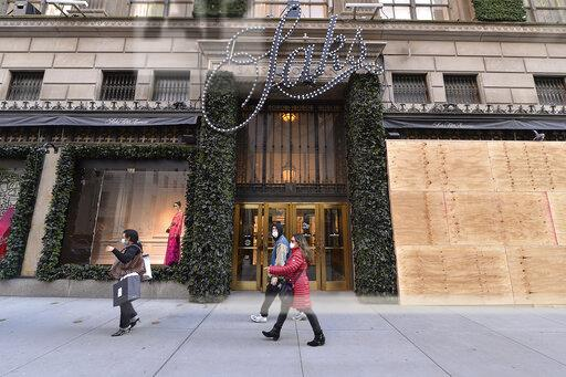 Pedestrians walk past the boarded up windows of the Saks Fifth Avenue flagship in New York on Saturday.