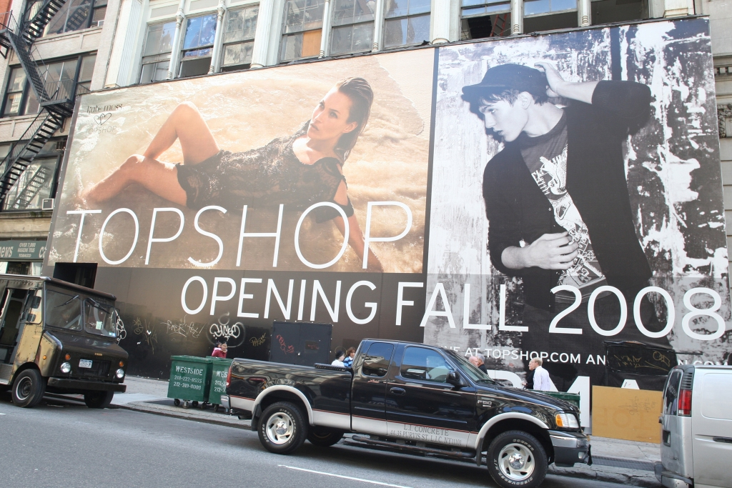 A sign advertising the opening of Topshop in NY.