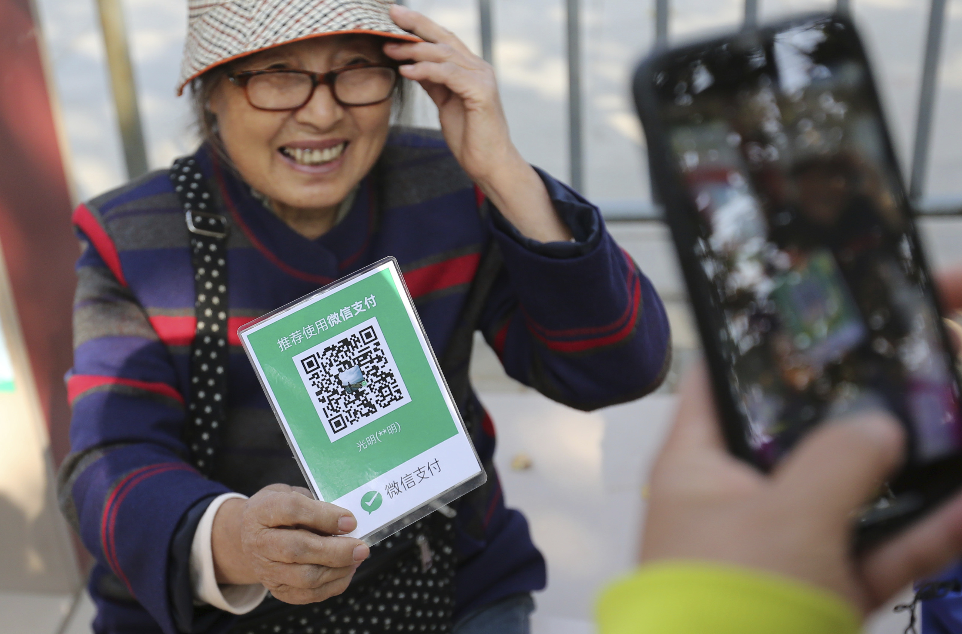 A local resident uses her smartphone to have the QR code scanned through the mobile app of Tencent's WeChat Payment function to pay her purchase.